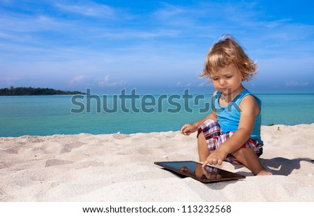 cute blond 2 years old kid playing tablet pc - stock photo