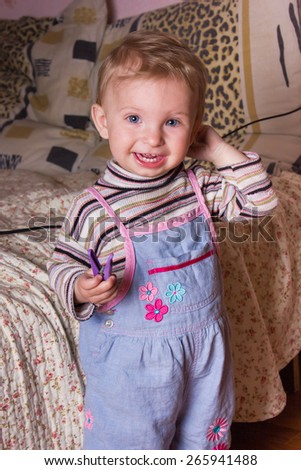 Cute blonde baby girl with beautiful blue eyes stands and smiling - stock photo