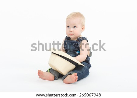 Cute blonde blue eyed baby boy sitting on the ground with white adult hat - stock photo