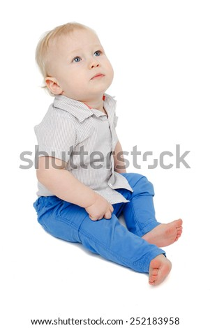 cute blonde blue eyed baby boy sitting over white background and looking up - stock photo