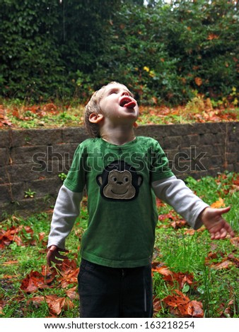 Cute Blonde Boy Gleefully Catches Raindrops on his tongue - stock photo