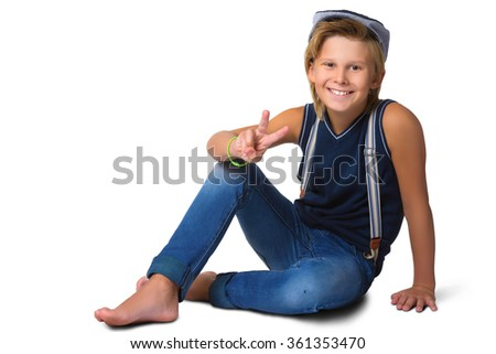 Cute blonde boy or teenager in full length casual style blue jeans posing and showing thumbs up isolated on white