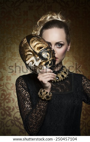 cute blonde female with antique lady style covering her face with precious mask and looking in camera. Wearing gothic lace dress and baroque jewellery