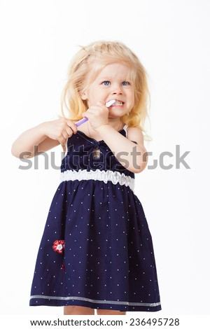Cute blonde girl cleans teeth on white background - stock photo