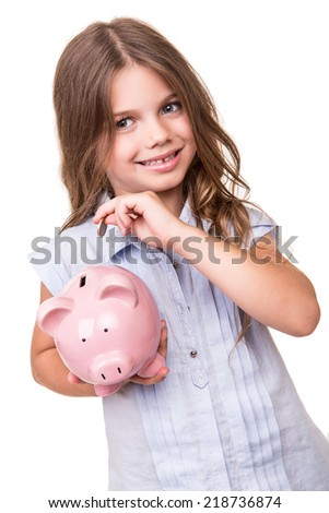 Cute blonde girl holding pink piggy bank