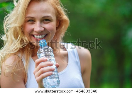 Cute blonde girl holding plastic bottle of water