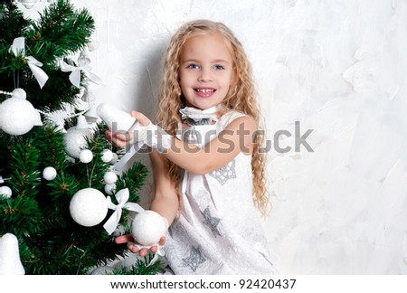 Cute blonde girl in white fancy dress near Christmas tree with white decorations - stock photo