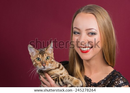 Cute blonde girl posing in the studio. Beautiful blue eyes. Girl with Bengal cat. Beauty, beauty, fashion. Photo Catalog. Portrait of a young girl. Girl with beautiful healthy hair. - stock photo