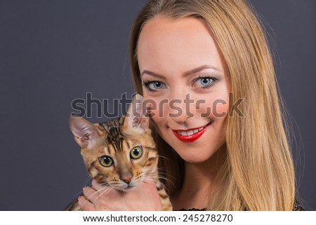 Cute blonde girl posing in the studio. Beautiful blue eyes. Woman with Bengal cat. Beauty, beauty, fashion. Photo Catalog. Portrait of a young girl. Girl with beautiful healthy hair. - stock photo