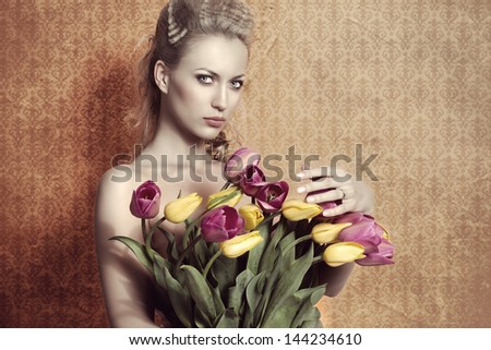 cute blonde girl with fashion hair-style and naked shoulders taking colourful floral bouquet in the hand and looking in camera on vintage background - stock photo