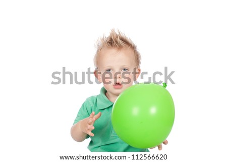 Cute blonde hair blue eyed baby boy wearing green top and holding green balloon on his birthday celebration - stock photo