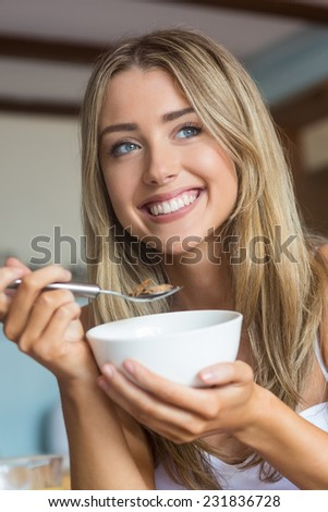 Cute blonde having cereal for breakfast at home in the kitchen