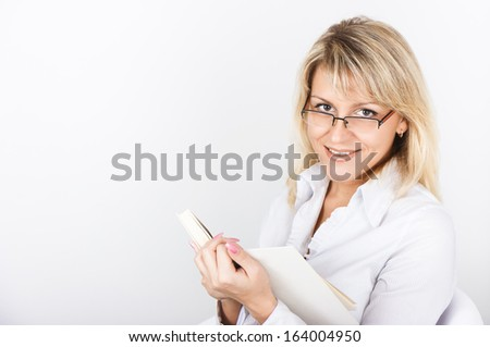 Cute blonde in glasses holding White Book - stock photo