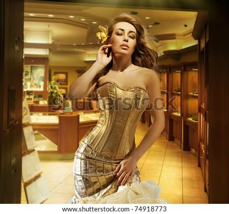 Cute blonde lady wearing golden dress in a jewelry shop - stock photo