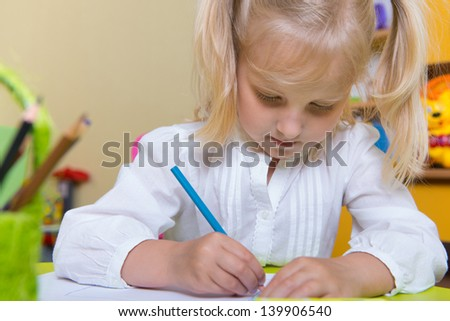 Cute blonde little girl drawing at school - stock photo