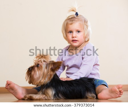 Cute blonde little girl on the floor with Yorkshire Terrier indoor - stock photo