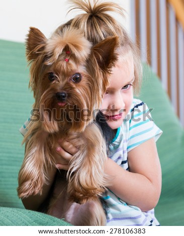 Cute blonde little girl playing with Yorkshire Terrier on sofa indoor