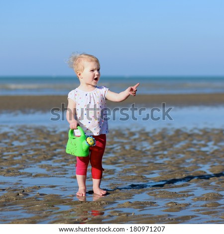 Cute blonde little toddler girl in colorful outfit plays with watering can at a shore of the sea on a long calm peaceful beach on a warm sunny summer day