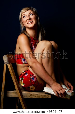 Cute blonde sitting on a wooden chair - stock photo