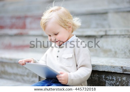 Cute blonde toddler boy playing with a digital tablet outdoors - stock photo