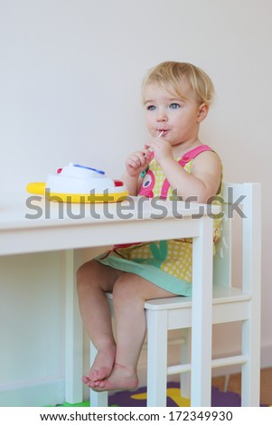 Cute blonde toddler girl eating lollipop