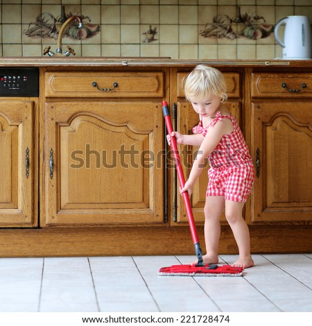 Cute blonde toddler girl helping with housekeeping in classical kitchen with wooden cabinetry cleaning tiles floor with wet flat mop - stock photo