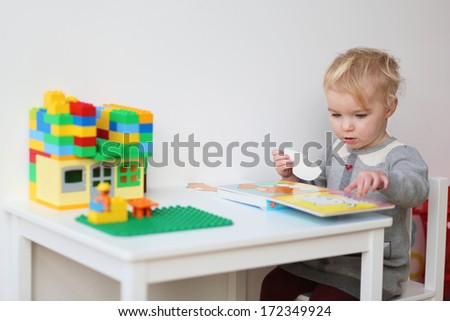 Cute blonde toddler girl solving puzzles in the book sitting at little white table indoors at home or kindergarten - stock photo