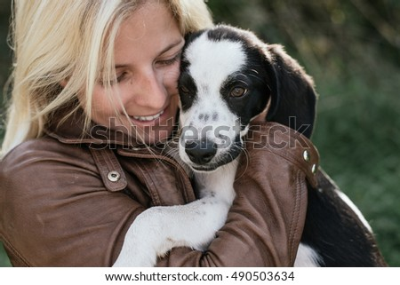 Cute blonde woman and her puppy playing outdoor