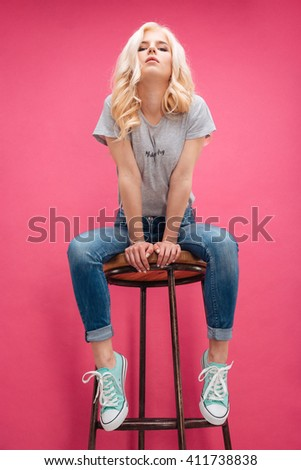 Cute blonde woman sitting on the chair and looking at camera over pink background - stock photo