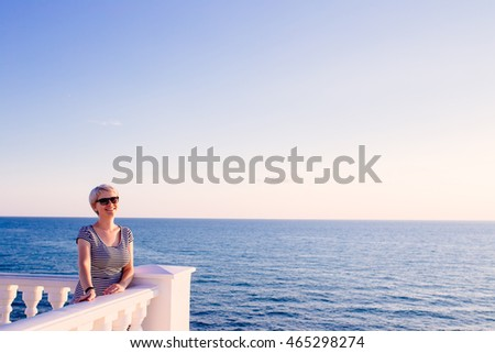 cute blondy woman on balcony looking at the ocean. travel concept