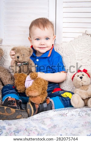 Cute blue-eyed baby sitting on a bed and playing with a teddy bear.