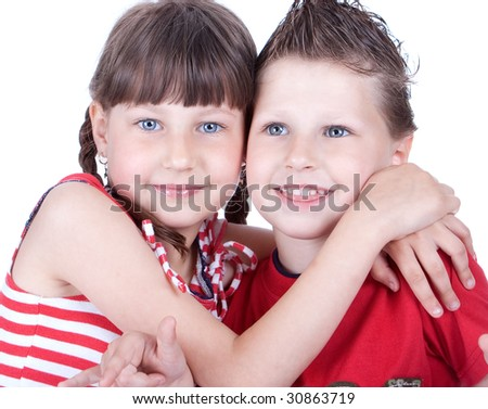 Cute blue-eyed boy and girl hugging each other, studio shot - stock photo