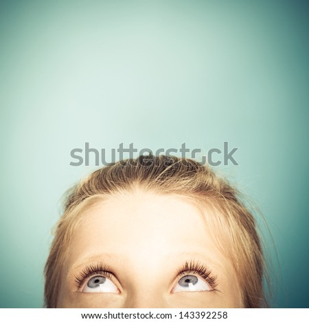 Cute blue-eyed girl looking up. - stock photo