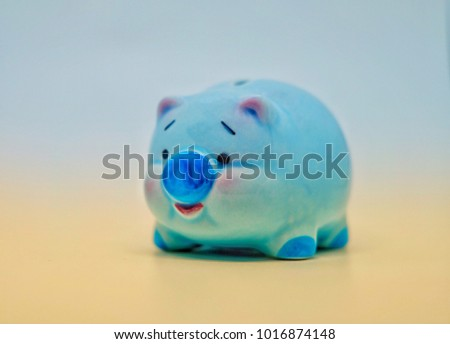 Cute blue piggy bank for saving money with orange light below half of photo isolated on white background, investment and business concept.