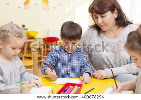 Cute boy, a pupil of the kindergarten, draws at the yellow table, along with the other pupils. Educator, beautiful mature woman watching him and smiling. Horizontal color image. - stock photo