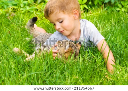 Cute boy  and cat lying in the grass