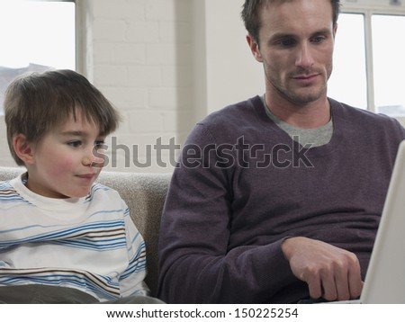 Cute boy and father looking at laptop in house - stock photo
