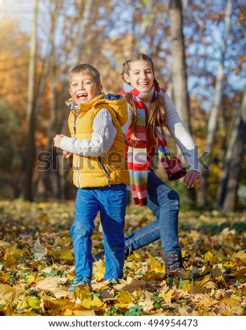 Cute boy and girl having fun with yellow leaves in autumn park