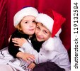 Cute boy and girl in Santa's hats with presents - stock photo