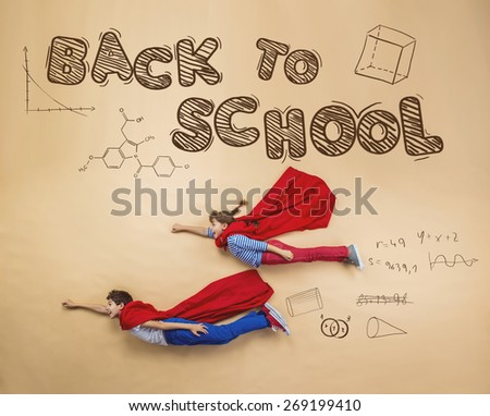 Cute boy and girl learning playfully in frot of a big blackboard. Studio shot on beige background. - stock photo