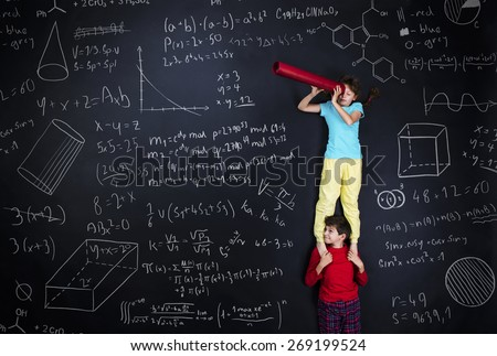Cute boy and girl learning playfully in frot of a big blackboard. Studio shot on black background. - stock photo
