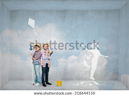 Cute boy and girl of school age painting wall with roller - stock photo