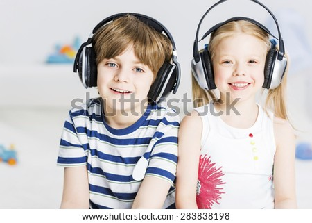 Cute boy and girl playing game in wireless headphones - stock photo