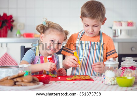 Cute boy and girl preparing Christmas cookies at home - stock photo