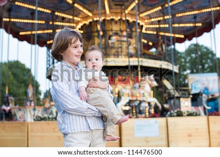 Cute boy and his baby sister standing in front of a carousel - stock photo