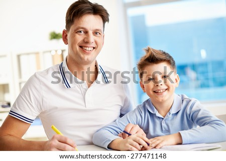 Cute boy and his father doing schoolwork together - stock photo