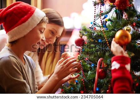 Cute boy and his mother decorating Christmas tree for holiday - stock photo