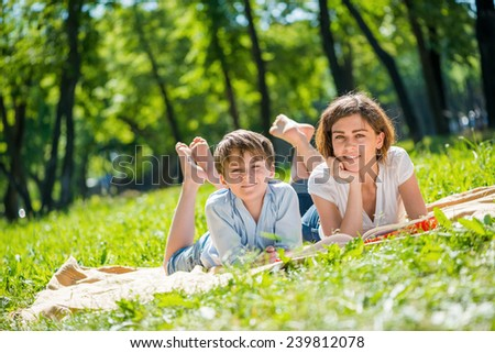 Cute boy and young woman in summer park laying on grass