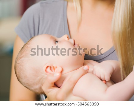 Cute boy baby son in mothers hands parents care