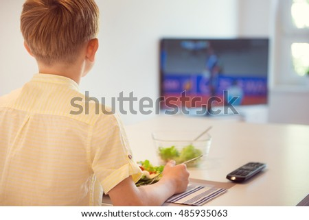 Cute boy child eating at the table in kitchen and watching football